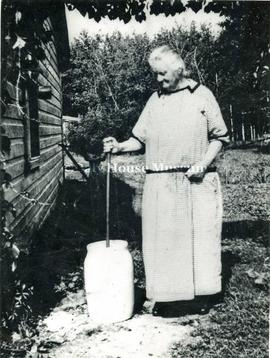 Elderly Woman Churning Butter