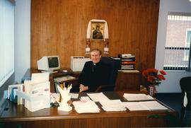 Unidentified clergy sitting at Metr. Michael Bzdel's desk